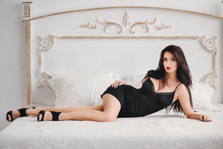 beautiful young sexy brunette with long hair lying on the bed photo