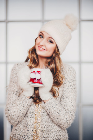Beautiful girl with long hair in winter hat smiling photo