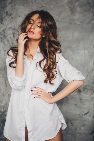 cuerpos desnudos: hermosa chica sexy con el pelo largo en una camisa mans con patas largas