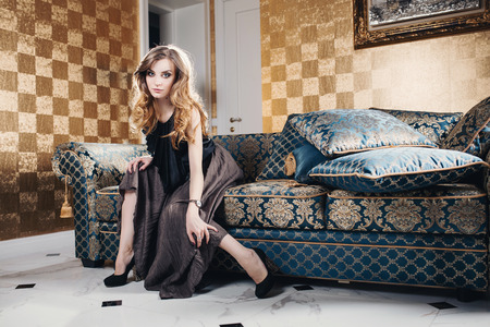 Beautiful young girl with beautiful eyes and long hair sitting in the room photo