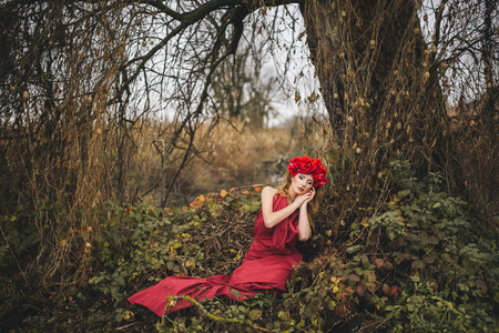 portrait of beautiful girl with red wreath on his head photo