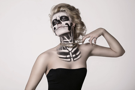 chica en la cara de la chica esqueleto en la cara del esqueleto Foto de archivo