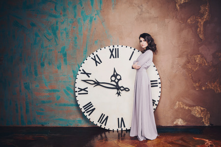 beautiful girl in a long dress about big clock