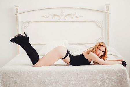 ベッドに横になっている黒のランジェリーで美しいスリムな女の子