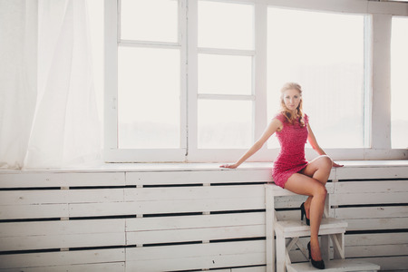 beautiful girl in ping dress sitting on a chair photo