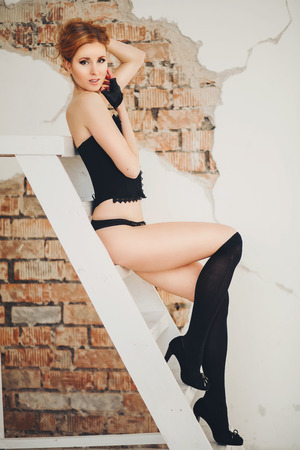 beautiful slim girl in black lingerie lying on the bed