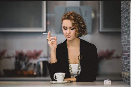 beautiful girl model looks with a cigarette looks straight photo