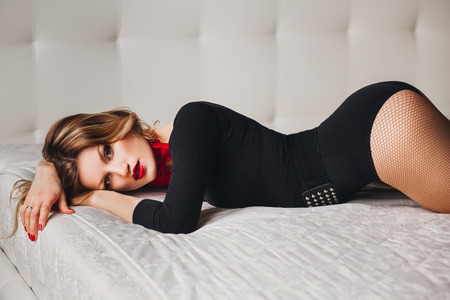 red butterfly: Beautiful girl in black body with red butterfly and red lips lying on the bed