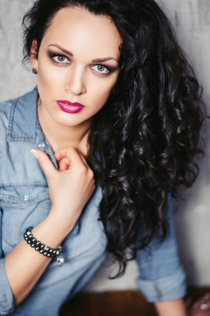 shocking: beautiful brunette girl with curly hair in a denim shirt Stock Photo