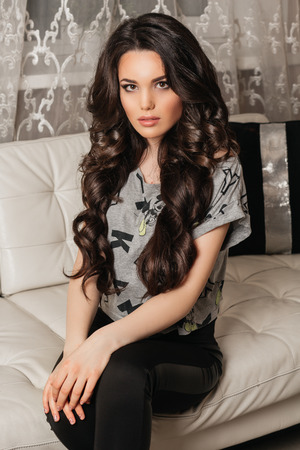 beautiful girl with long dark curly hair silit on the couch