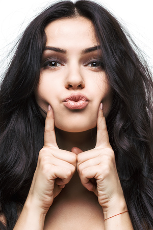 finger on lips: Blowing a kiss from beautiful young woman, isolated Stock Photo