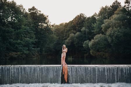 beautiful woman on the waterfall in a long dress