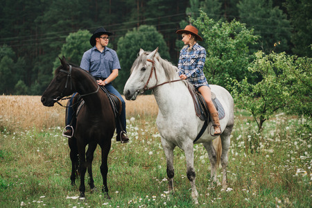riding boot: loving couple man and woman in a cowboy hat riding a horse Stock Photo