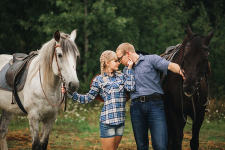 stead: loving couple man and woman in a cowboy hat riding a horse Stock Photo