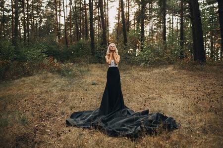 sensual: hermosa delgada rubia en vestido largo negro en el bosque Foto de archivo