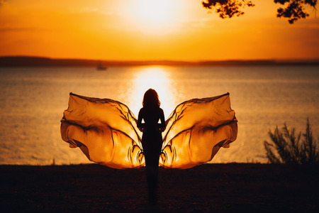 donna farfalla: silhouette al tramonto sul tessuto ondeggiamento mare nella forma di una farfalla Archivio Fotografico