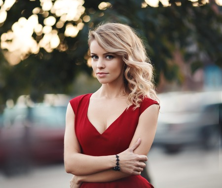 glamour woman: portrait of sexy caucasian young woman in red dress with long blond hair, beautiful eyes, sensual lips and clean skin
