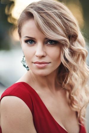 girl sexy: retrato de mujer joven caucásica atractiva en el vestido rojo con el pelo largo y rubio, ojos hermosos, sensuales labios y la piel limpia