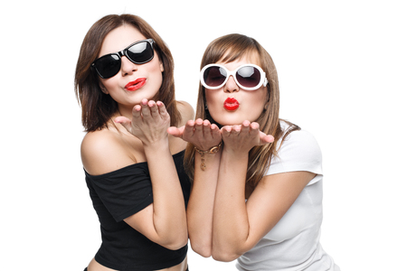 hot teen girl: Glamorous stylish young women model with red lips in a black and white bright hipster clothes and sunglasses send a kiss