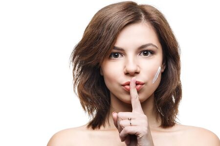 cheek to cheek: beautiful girl isolated on white background, clean skin with cream on her cheek Stock Photo