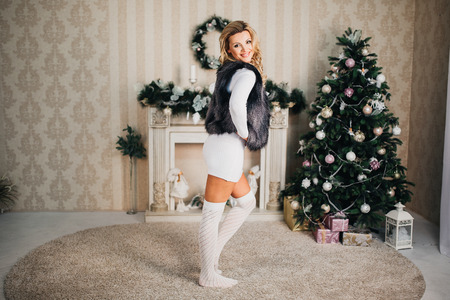 Very beautiful blonde girl inin a white dress and socks sitting on the background of the Christmas tree and fireplace