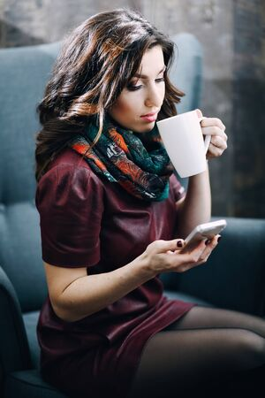 corresponds: Beautiful girl with beautiful makeup drinking tea or coffee in cafe and looking at the phone. chat online with a friend, corresponds with a friend, young woman drinking tea coffee and chat online Stock Photo