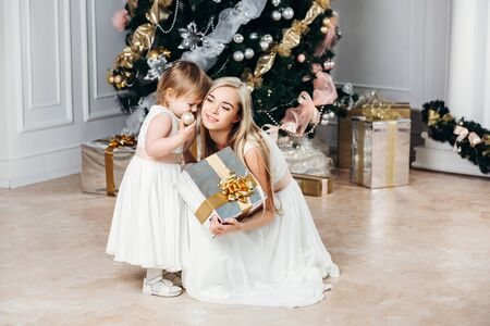 happy family mother and daughter at Christmas and New Year with gifts around the Christmas tree. in Christmas, in identical white dresses, New Years concert, Merry Christmas, Mom daughter indulges Stock Photo