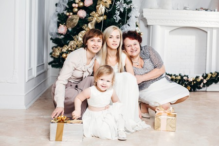 grandmother mother daughter: christmas, x-mas, winter, happiness concept - smiling happy family: grandmother, mother, daughter, granddaughter around the Christmas tree with gifts, 4 generations of the family, four, love concept Stock Photo