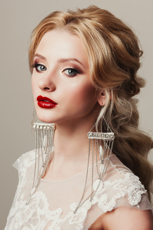 female sexy chains: Glamour portrait of a beautiful female model with red lips and long blond hair in a luxurious stylish trendy earrings. Shiny long unusual luxury earrings Stock Photo
