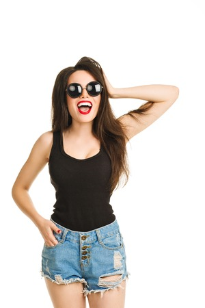 going crazy: Fashion glamor sexy girl with beautiful snow-white smile, fun going crazy resting, cries. Stylish brunette girl in jeans and hipster outfit. Isolated white background. Fashion round glasses red lips Stock Photo