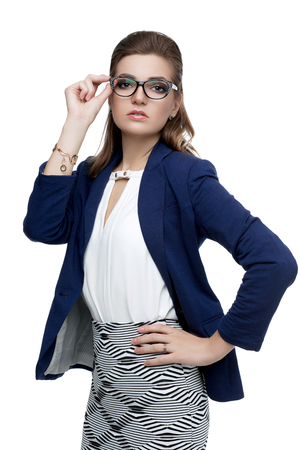 Business Woman in Glasses on a White Background. Beautiful sexy woman with an evening make-up natural red lipstick in stylish glasses for vision. Glamorous young woman in blue jacket. Fashionable. Banco de Imagens