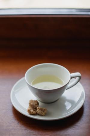 tea service: tea cup, white mug, saucer, cane sugar on a saucer, white tea service Stock Photo