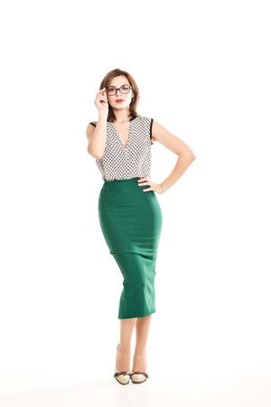 falda: Hermosa chica morena con gafas de luz blusa verde y falda ajustada sobre un fondo blanco, maquillaje de moda