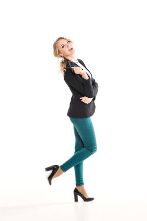office wear: Beautiful blonde girl in a black jacket, purple pants and high heel shoes, office wear, luxury fashion make-up, on a white background in the studio, posing for the camera