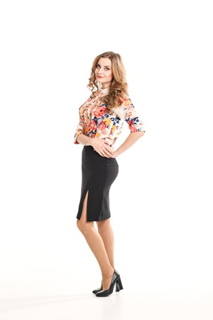 office shoes: beautiful young blonde woman in office clothes on a white background, in a blouse with flowers black skirt and shoes with heels in the studio, posing for the camera, fashionable luxury makeup