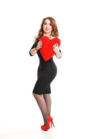 make love: Hermosa morena sexy mujer presente coraz�n rojo, el d�a de San Valent�n. modelo elegante chica con estilo de pelo largo y ondulado, maquillaje. Dama en vestido de lujo aislado en el fondo blanco.