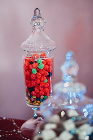 raspberry jelly: fruity red raspberry jelly beans in a flask of glass, full glass, beautiful delicious dessert, decor