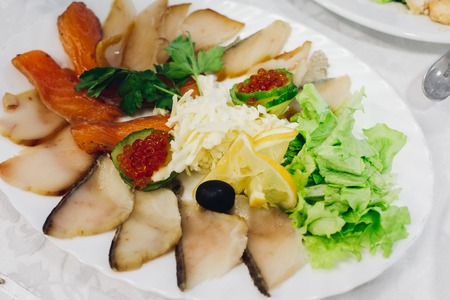 Overhead view of smoked salmon and cheeses served with fresh salad and garnish with lemon, fish platter