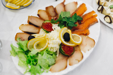 sturgeon: Slices of fish and black olives on a plate with lemon, sliced fish platter with fresh salad