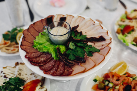 roast meat: Group of thin sliced meat and sauce. Assorted cold meat platter artistically arranged. Salami. Assorted meat products. A variety of processed cold meat products. Tasty sliced sausage