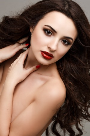 human lips: portrait of sexy young woman with long dark hair, beautiful eyes, sensual red lips and clear skin, beautiful hair, piercing gaze straight on stranded hair, curly hair, earring jewelry. Luxury makeup Stock Photo