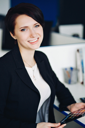 Young business woman wearing a suit using a tablet computer and looking at camera. Young gorgeous businesswoman holding in hands digital tablet,successful female CEO dressed in elegant clothes posing Stock Photo