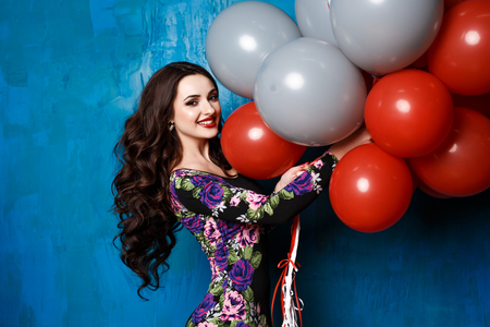 party people: Happy young woman with colorful latex balloons. beauty, people, style, holidays and fashion concept - happy young woman or teen girl in dress with helium air balloons