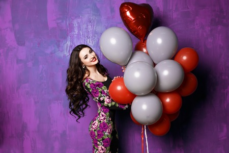 Happy young girl with big colorful latex balloons. Beauty Romantic Girl Indoors. Woman with long wavy hair having fun. Brunette with bright colored balloons in a long bright flowered dress Banco de Imagens