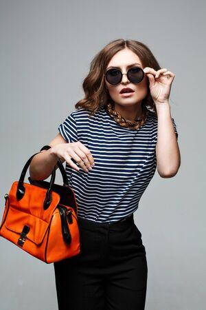 saddlebag: woman hands holding orange bag. Street look. Fashion look. Street style. Autumn outfit. Fashion model. Urban fashion. Stock Photo