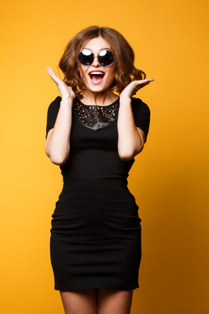 Studio spring fashion portrait, bright details, sweater sunglasse, dress, happy joyful emotions, jumping dancing and smile bright colors, gray background. Banco de Imagens
