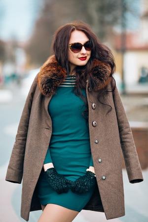 poses de modelos: atractiva chica morena glamorosa, bella mujer joven con el pelo largo elegante oscuro, con gafas de sol con estilo, vestido verde de moda por capas elegante con la piel suave y esponjosa y guantes al aire libre maquillaje de moda