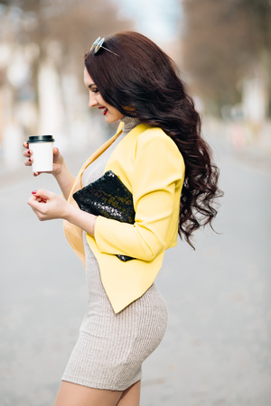 yellow jacket: A businesswoman talking via mobile phone and holding a coffee cup. Young slim stylish girl in bright clothes, yellow jacket, a wonderful long dark curly hair holding a cup of coffee and a fashionable black handbag