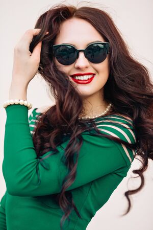 mirrored: Funny model in sunglasses and in a little green dress, white background.