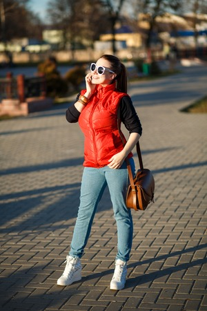 tied down: Girl in town, dressed in a red vest, a dark jacket, jeans, hair tied up in a ponytail, red bag. The girl looks in the bag. The round sunglasses. Walks down the street. The background is blurred. Stock Photo